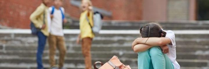Girls sitting on a step, other children on the background pointing and laughing at her. Tyttö istuu portailla nojaten käsiinsä. Taustalla muut lapset osoittelevat häntä ja nauravat.