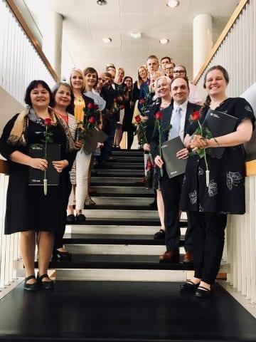JOKO -koulutuksesta kesäkuussa 2019 valmistuneet juhlapäivänä portaikoissa pitäen kädessään ruusuja ja todistuksia