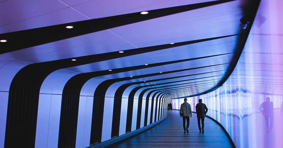 Kaksi henkilöä kävelee futuristisen käytävän läpi. Konsortio-ohjelmien kansikuva, konsortio-ohjelma kehittää yritystä ja johtajuutta.