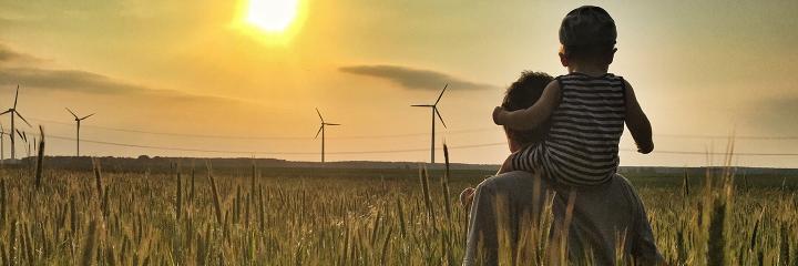 Aikuinen ja lapsi katselevat tuulivoimaloita pellolla