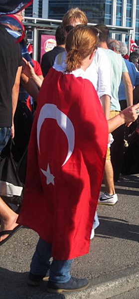 Turkkilainen nainen kietoutuneena Turkin lippuun. Kuva: Riina Keto-Tokoi.