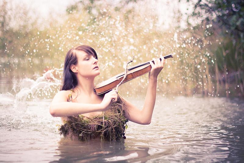 Toukokuun kalenterityttönä Kukka-Maaria Wessman esittää Näkkiä, joka viettelee viulunsoitollaan uhrinsa veteen. Kuva: Eino Nurmisto.