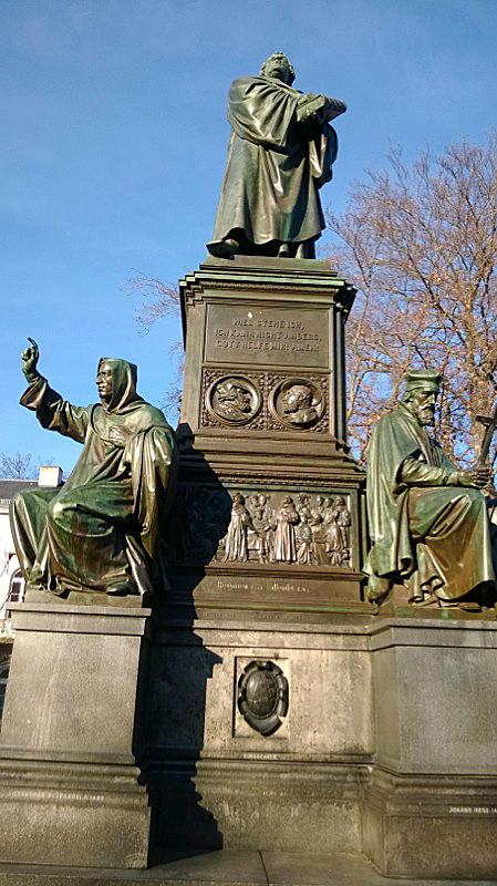 """""""Hier stehe ich, ich kann nicht anders, Gott helfe mir, amen!"""" Luther Wormsin valtiopäivillä 1521. Luther-monumentti Wormsin kaupungissa vuodelta 1868. Alhaalla vasemmalla kuvattuna Hieronymus Savonarola, oikealla Jan Hus. Kuva: TUCEMEMS."""
