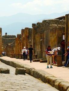 Turisteja Pompeijin Via Mercurion raunioilla aurinkoisena kesäpäivänä.