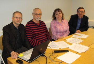 Ryhmäkuva, jossa kirjan kirjoittajat istuvat pöydän ääressä.