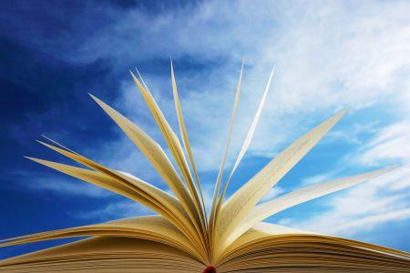 Pöydälle avatun kirjan sivuja kuvattuna sinistä taivasta vasten.