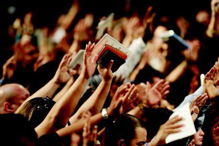 Suuri määrä ihmisiä nostaneena kädet ylös ylistykseen, yhdellä kädessään Raamattu.