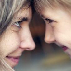 Vanhempi ja lapsi katsovat toisiaan hymyillen silmiin.