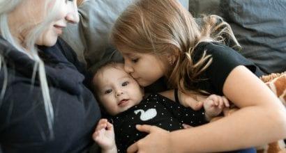 Äiti, vauva ja lapsi yhdessä sohvalla