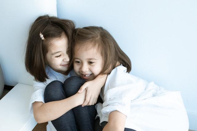 Kaksi iloista pikkutyttöä kaulakkain