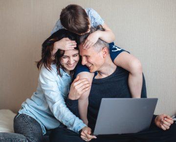 Vanhemmat ja lapsi yhdessä tietokoneen äärellä.