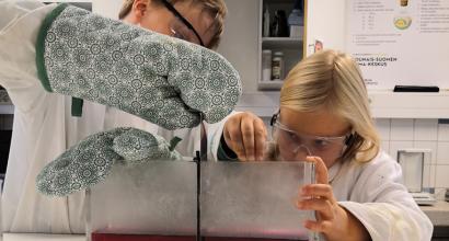 kaksi lasta laboratoriossa puuhaamassa