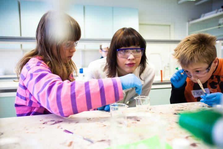 Lapset OpiLUMA-laboratoriossa ohjaajajn johdolla.