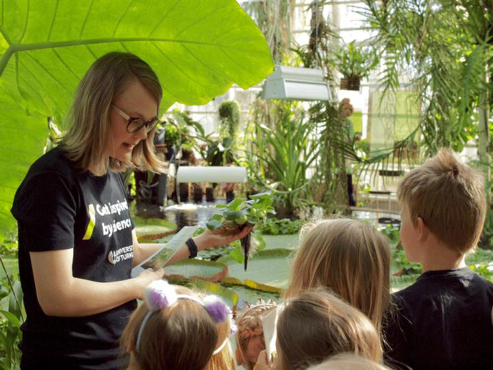 Lapset kasvitieteellisessä puutarhassa ohjaajan kanssa.