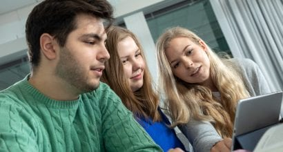 Kolme opiskelijaa iPadin äärellä.