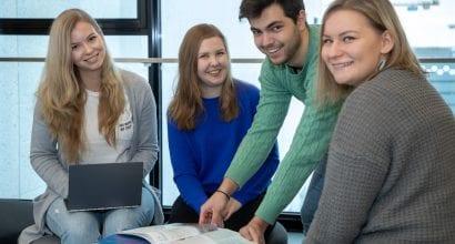 Neljä opiskelijaa katsoo kameraan.
