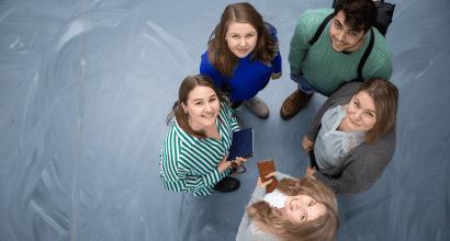 Opiskelijoita seisomassa ringissä katsomassa ylös kameraan.