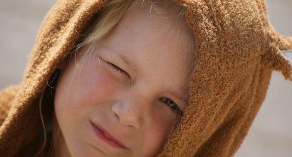 Lapsi karhuhuppu päässään.
