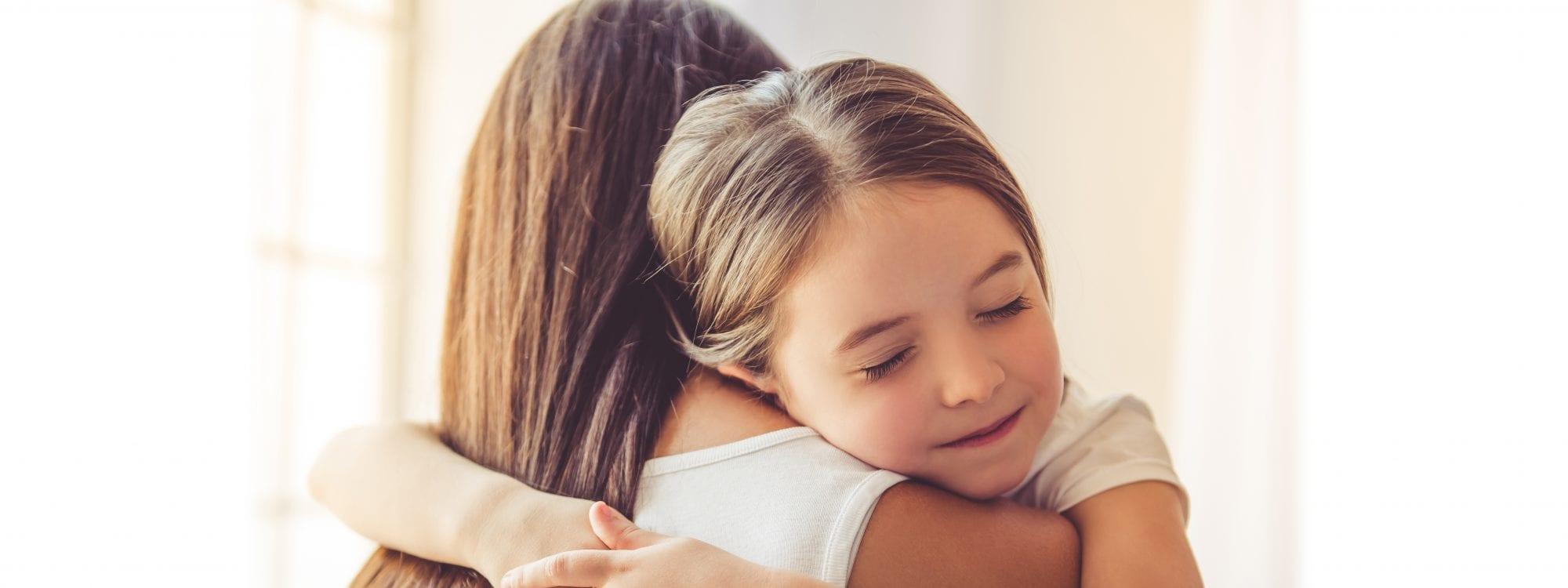 Bannerikuva, jossa vanhempi ja lapsi halaavat